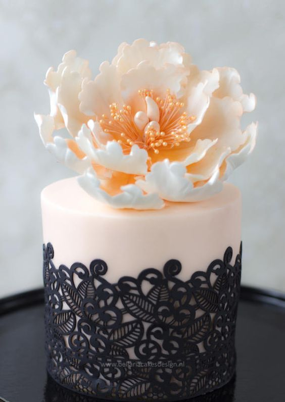 a blush and black lace mini cake with an open peony on top for a glam wedding