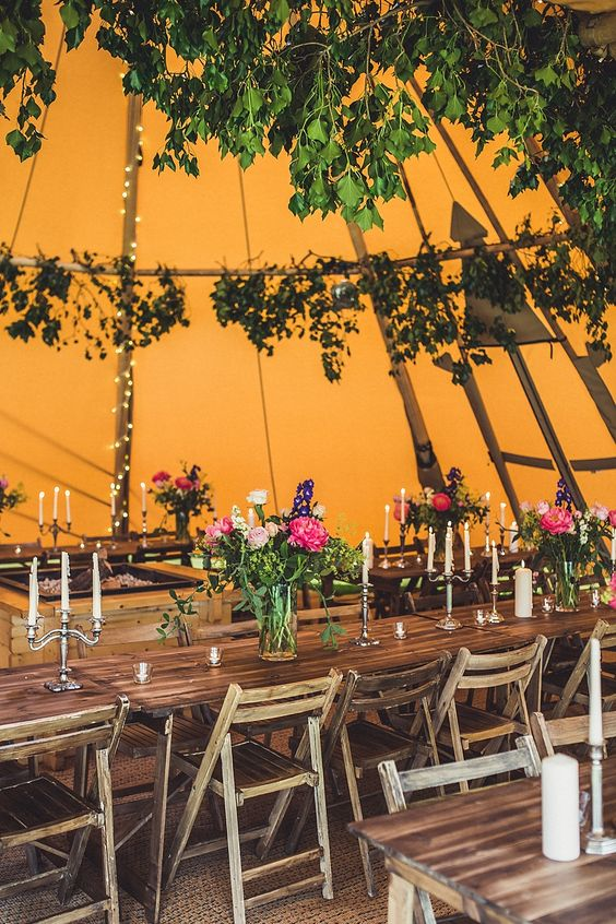 a bold orange tent with greenery and herbs, lights and candles for a fall woodland wedding