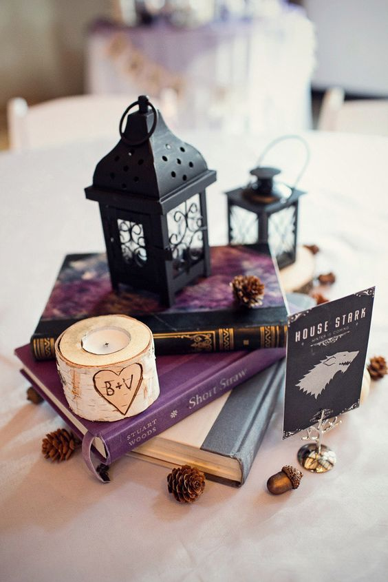 a book stack with black lanterns, a birch candle holder and pinecones for a winter wedding with a geeky touch