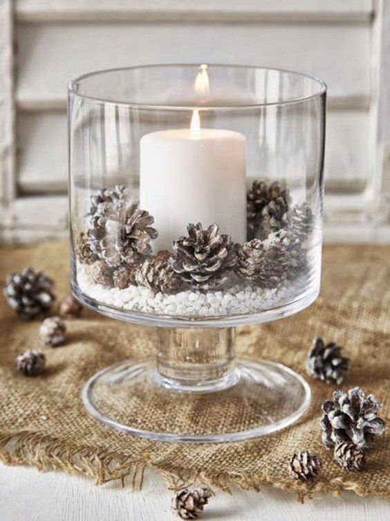 a glass bowl with faux snow, snowy pinecones and a large candle will add coziness to a wintr tablescape