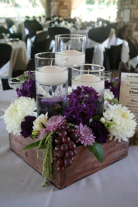 a lush vineyard centerpiece with blooms, grapes and floating candles in tall glasses