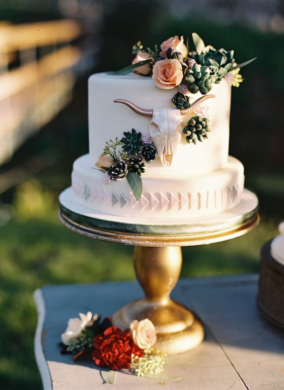 a wedding cake with flowers, greenery, succulents and a skull of sugar and cream