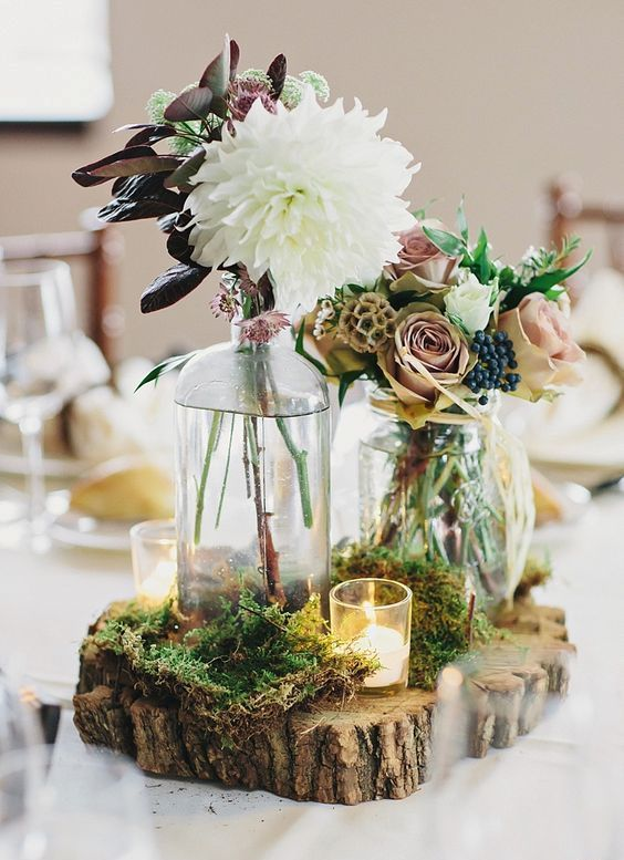 a wood slice covered with moss, with a candle and some beautiful flowers make a cool and laid back centerpiece