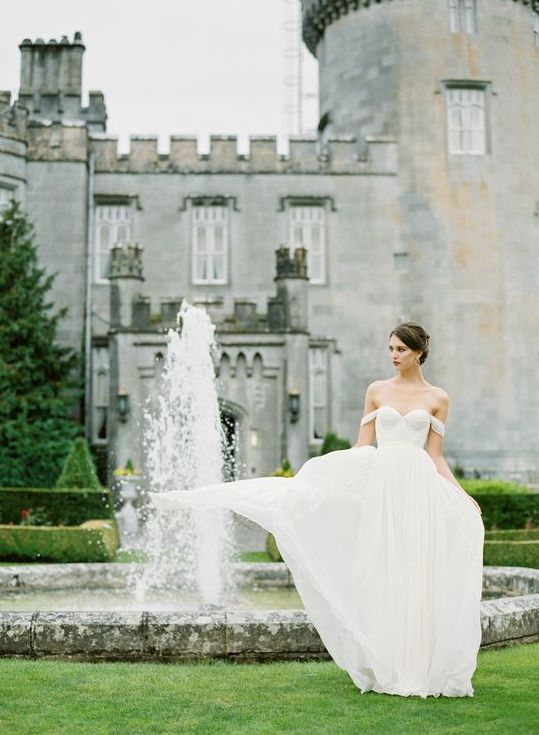 a bridal portrait taken in the castle backyard with fountains looks beautiful and relaxed