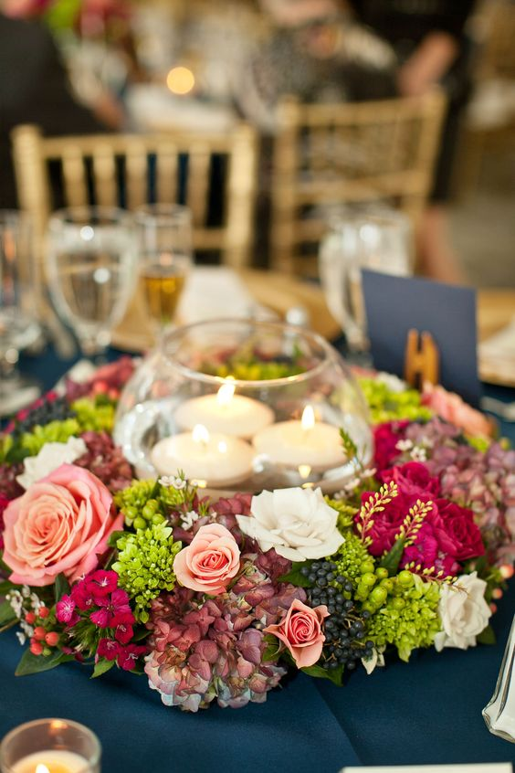a glass bowl with floating candles surrounded with lush florals and berries for a refined feel
