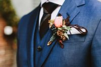 25 a navy three piece wedding suit, a striped tie and a floral boutonniere