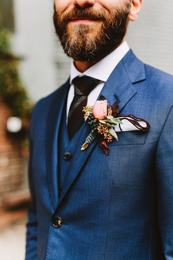 a navy three piece wedding suit, a striped tie and a floral boutonniere