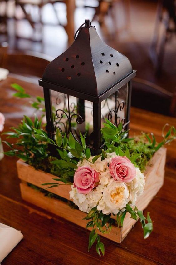 a pallet box with greenery, flowers and a black metal candle lantern for a rustic wedding