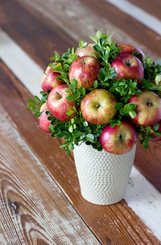 a white textural vase and an arrangement of boxwood and apples is an inexpensive and cute fall centerpiece
