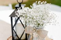 25 a wood slice with a candle lantern and a jar with baby's breath, a burlap bow with a pearl pin