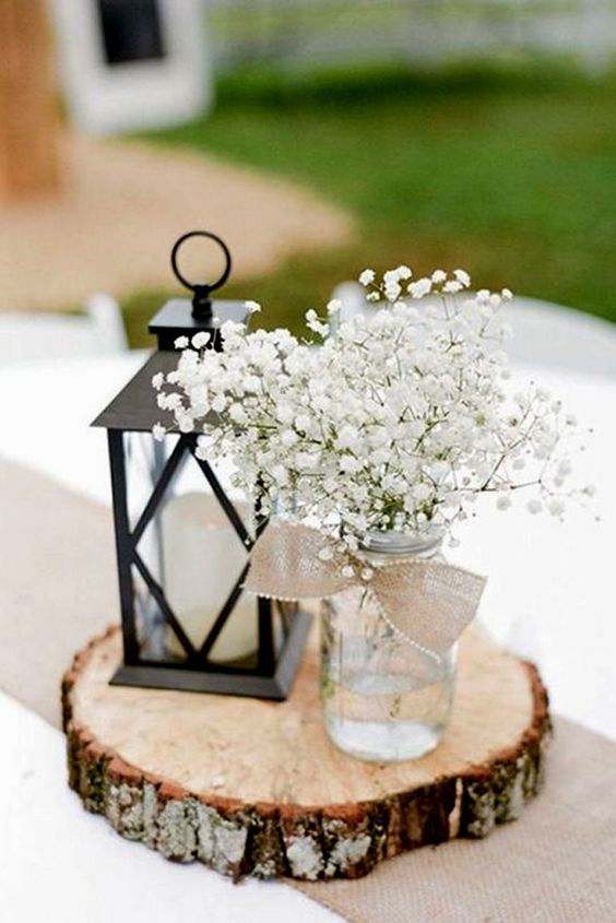 a wood slice with a candle lantern and a jar with baby's breath, a burlap bow with a pearl pin