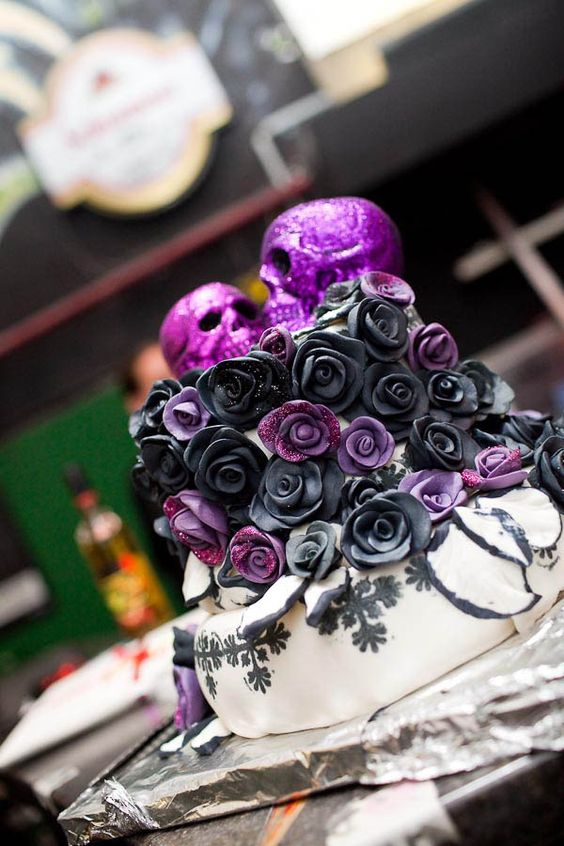 black, white and purple wedding cake with purple glitter skulls on top