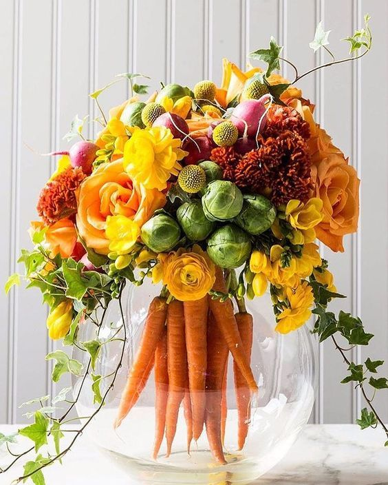 a bold centerpiece with carrots, cabbages, radish and yellow and orange flowers for a fall wedding