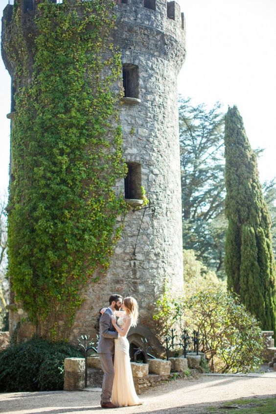 a couple portrayed in front of a castle tower covered with lush greenery looks intimate and heavenly