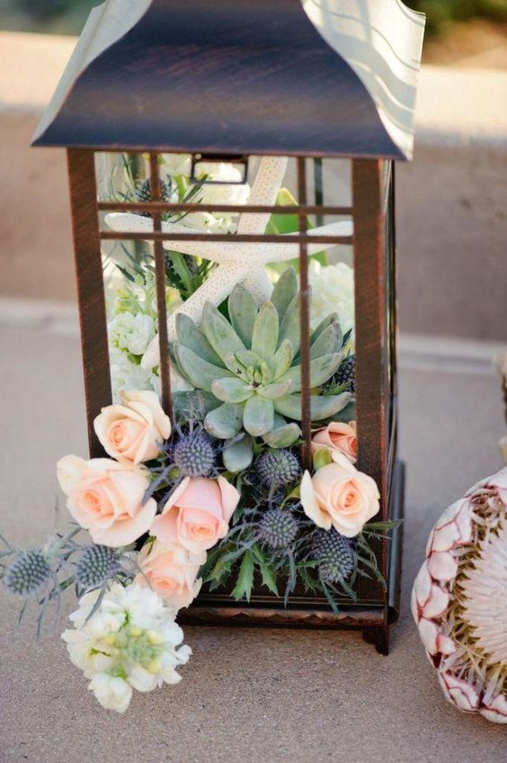 a metal candle lantern with pink roses, thistle, succulents and a star fish for a seaside wedding table