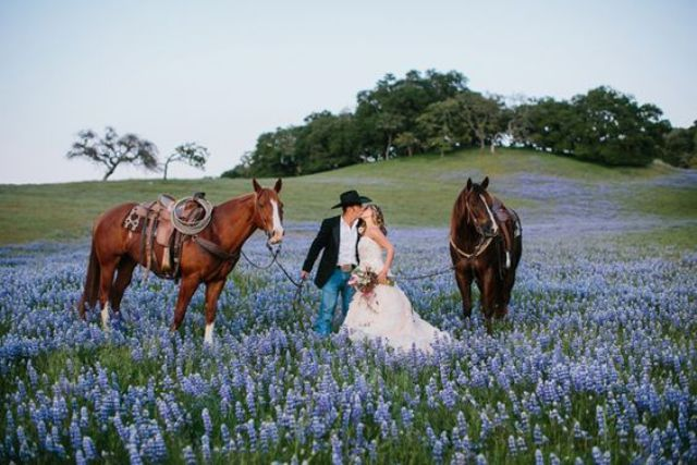 newlyweds wandering in the floral fields with horses