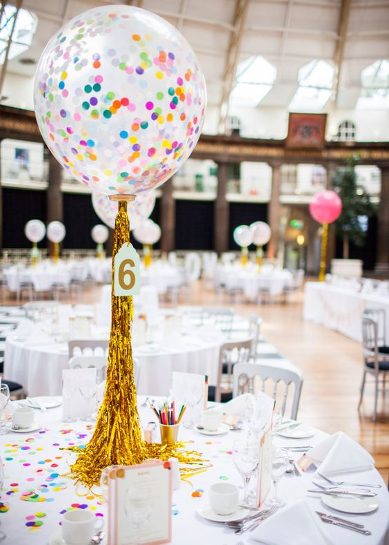 transparent balloons with colroful confetti inside and gold fringe for a centerpiece