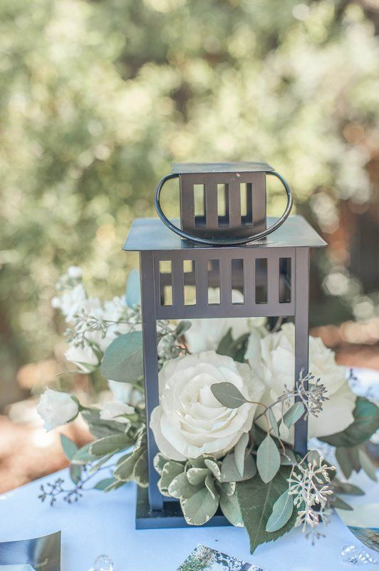 a metal lantern with white roses and foliage is a simple and romantic centerpiece for any wedding