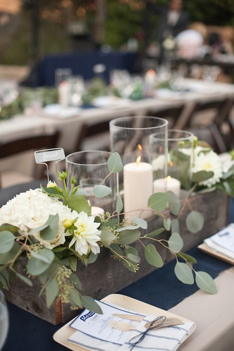 a reclaimed wooden box with white blooms, eucalyptus and candles for a chic look