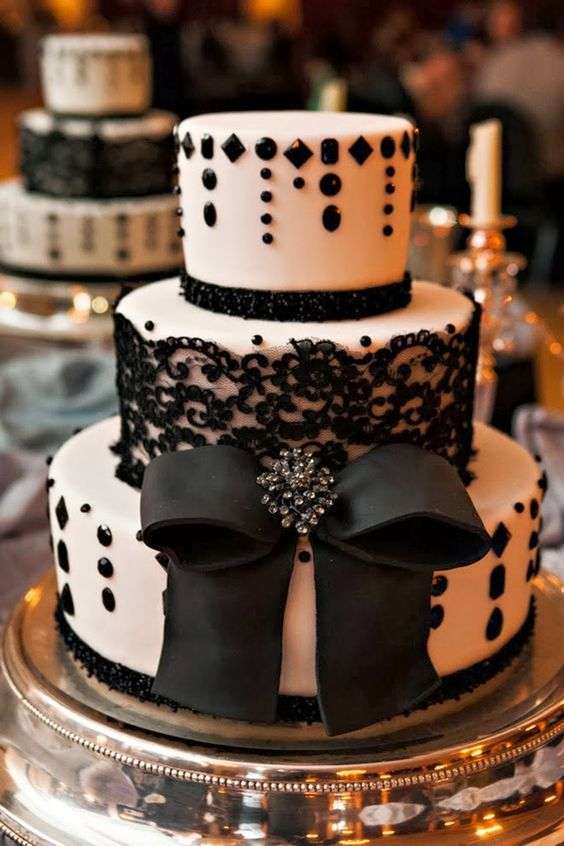 a white wedding cake decorated with beads and black lace, with a large edible bow for an elegant wedding