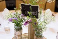 27 a wood slice with jars covered with burlap, jute and lace, wildflowers and a chalkboard table name