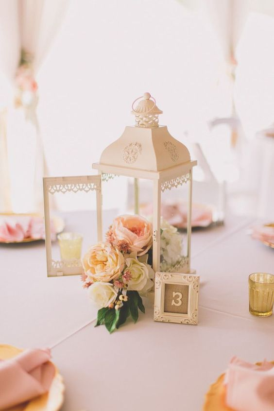a Morocco-style lantern with a pastel floral arrangement and a small framed table number