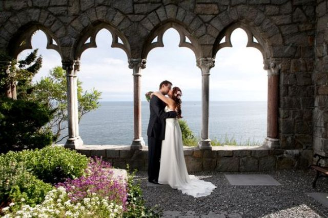 a couple's portrait taken on a terrace of Hammond Castle with gorgeous lake views