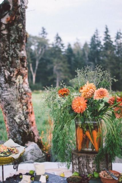 a rustic centerpiece of carrots, orange dahlias and herbs for a fall or Thanksgiving wedding