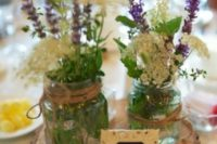 28 a wood slice, a chalkboard table number, jars wrapped with twine and wildflowers make up a cool centerpiece