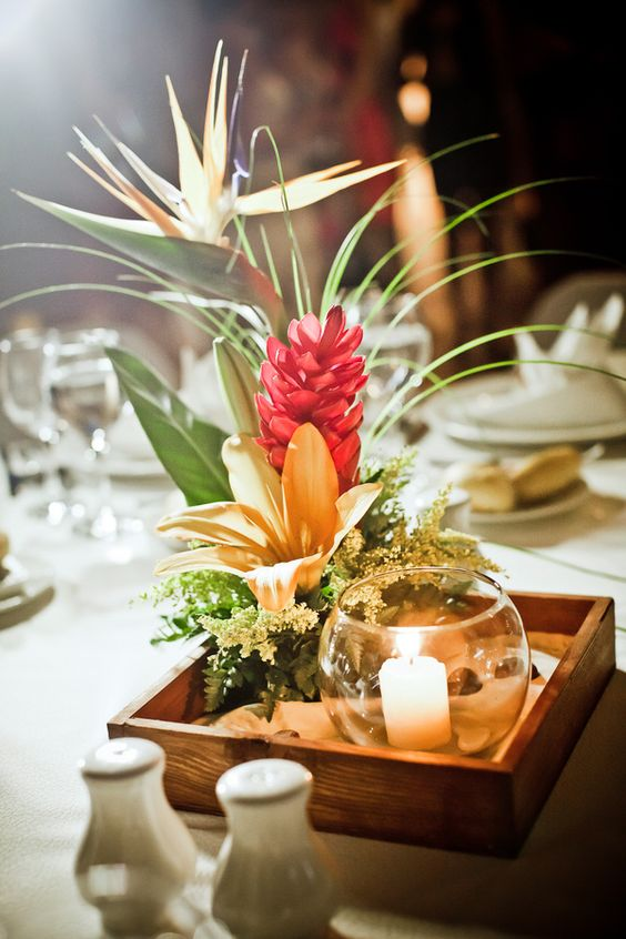 a wooden box with bold tropical blooms and leaves and a glass bowl with a candle