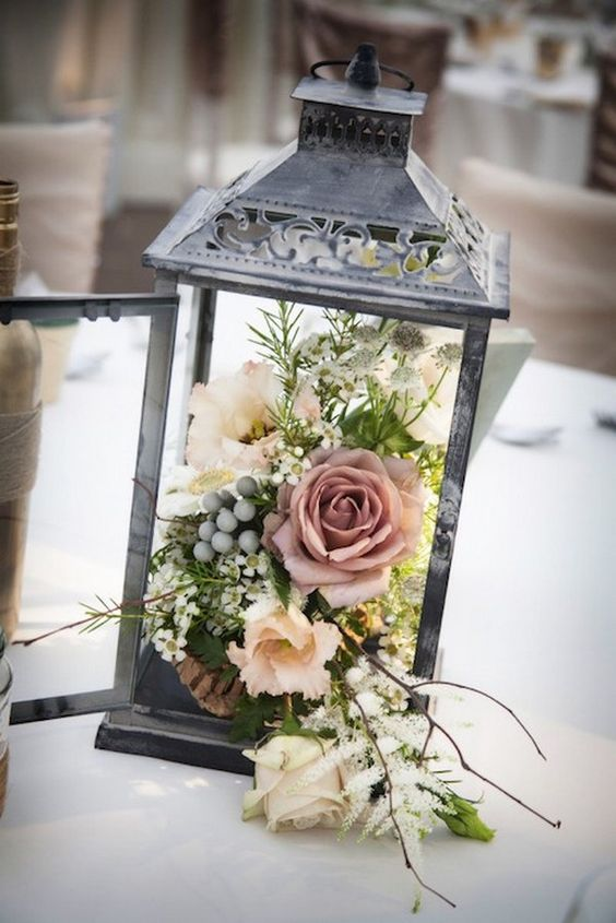 a shabby chic dark metal lantern with a textural floral arrangement looks chic and unusual