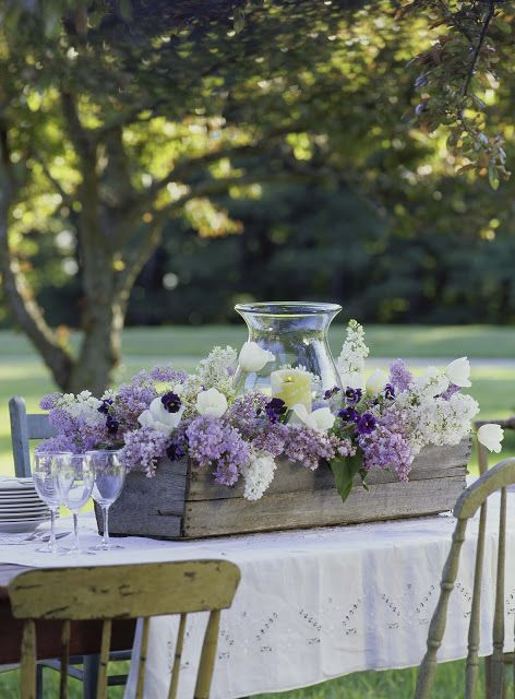 a wooden box with lilac, white blooms and a large glass candle lantern