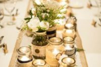 29 jars covered with lace and burlap, with candles inside and blooms and greenery