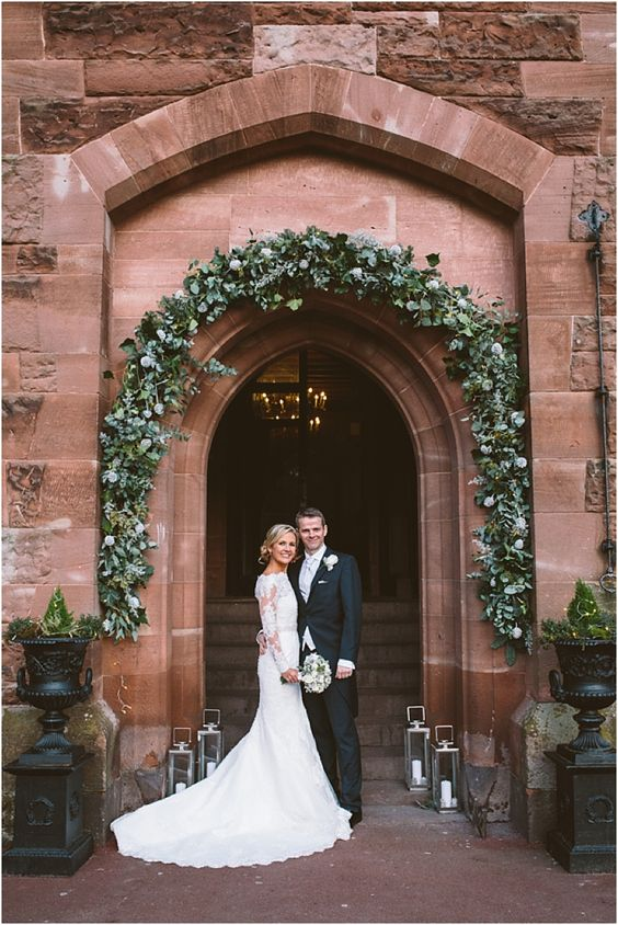a couple at the entrance to Peckforton Castle right after their ceremony