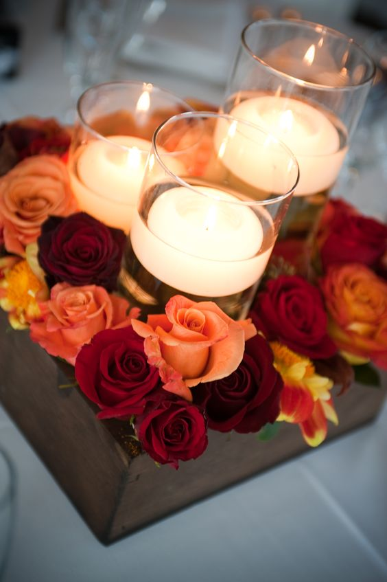 a dark stained box with red and orange roses and floating candles in tall glasses