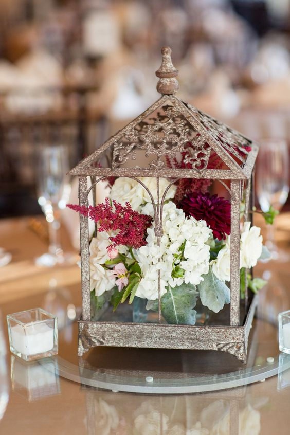 a shiny lantern with white, plum and marsala blooms inside and some candles around for a fall wedding table