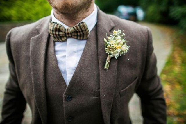 a three piece brown tweed suit with a plaid bow tie