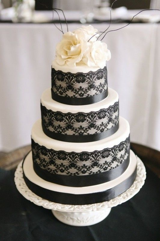 white and black lace and ribbon wedding cake with creamy flowers on top