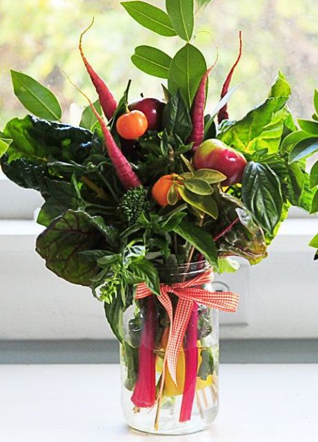 an organic centerpiece with cabbage, carrots, apples, herbs and fruits for a cozy fall wedding