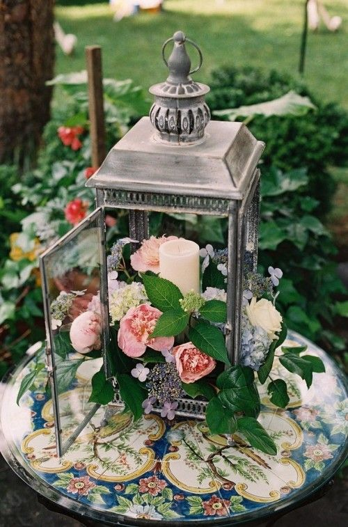 an antique lantern with pink, blue and neutral blooms and a candle on a gorgeous dish for a garden wedding table setting