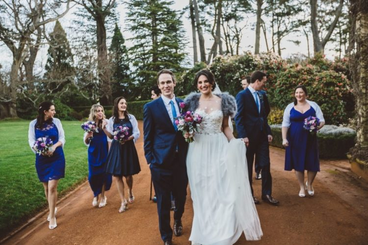 The bride was wearing a gorgeous lace bodice wedding dress, the bridesmaids were wearing cobalt blue dress, and guys were dressed in navy suits with matching ties