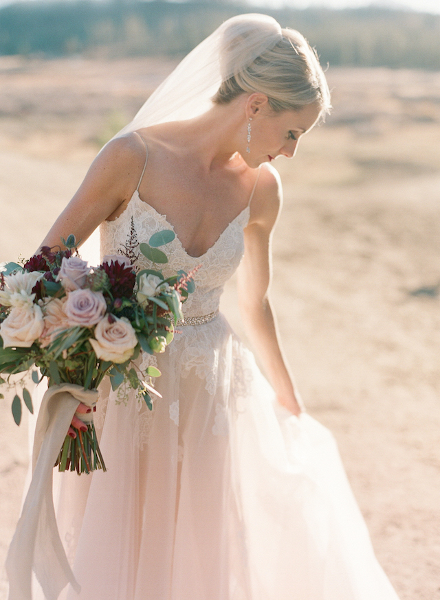 The bride was wearing a jaw-dropping blush wedding gown with spaghetti straps and white floral appliques by Monique Lhuillier
