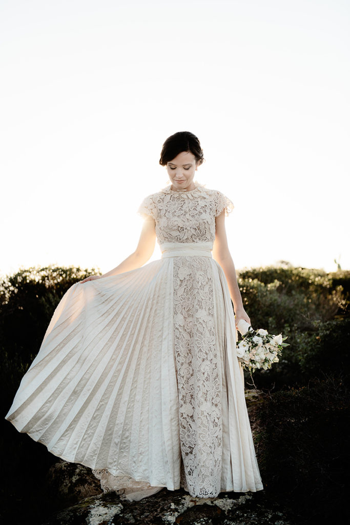 The bride was wearing a unique floral lace wedding dress with short sleeves, a sash and a pleated overskirt