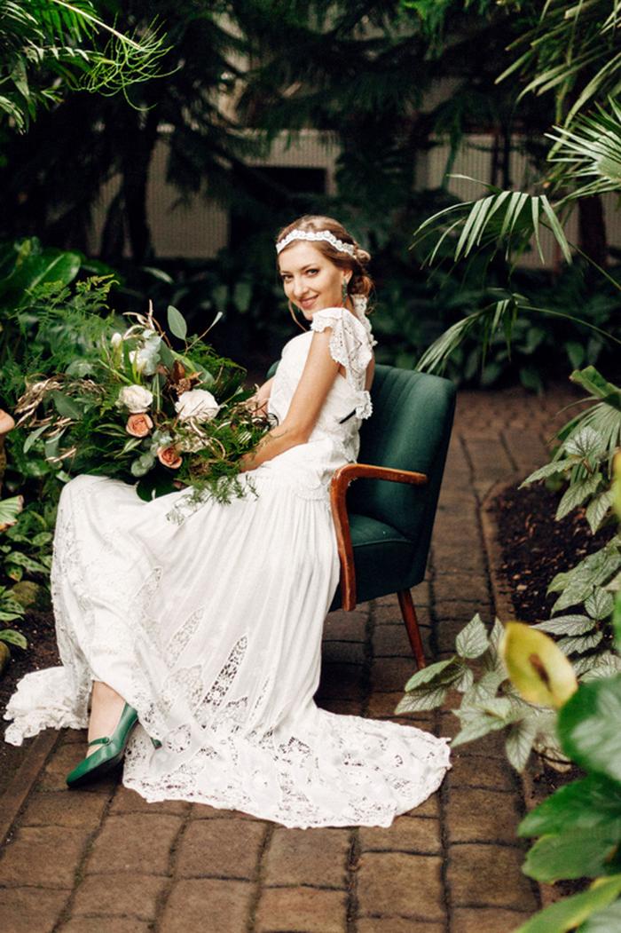 Die Braut trug ein vintage-inspiriert Spitzen Kleid mit einem offenen Rücken, emerald Schuhe, Ohrringe und ein Spitzen Stirnband
