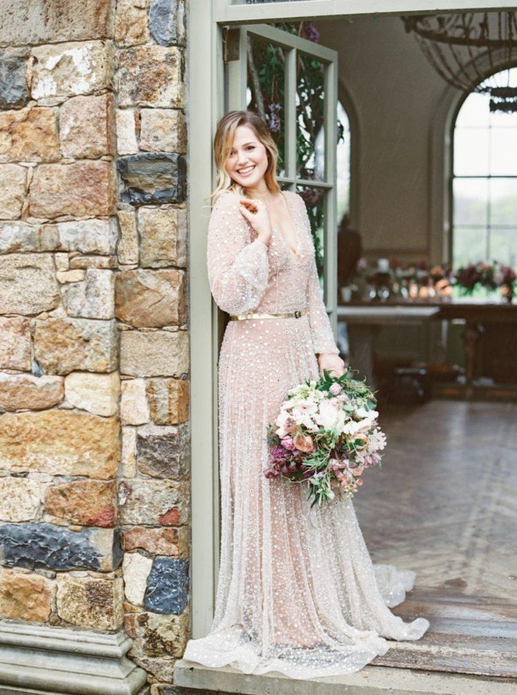 Die Braut trug eine unglaubliche schimmernde Hochzeitskleid mit langen ärmeln und tiefem Ausschnitt, akzentuiert mit einem metallic-Gürtel