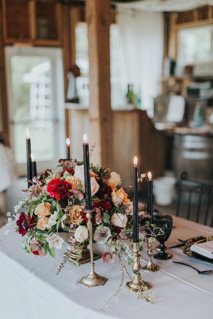Der Hochzeits-Mittelstück wurde mit Fett üppigen Blüten, mit roten, gelbe und orange Blüten und schwarze Kerzen und Kerzenhalter sah matching