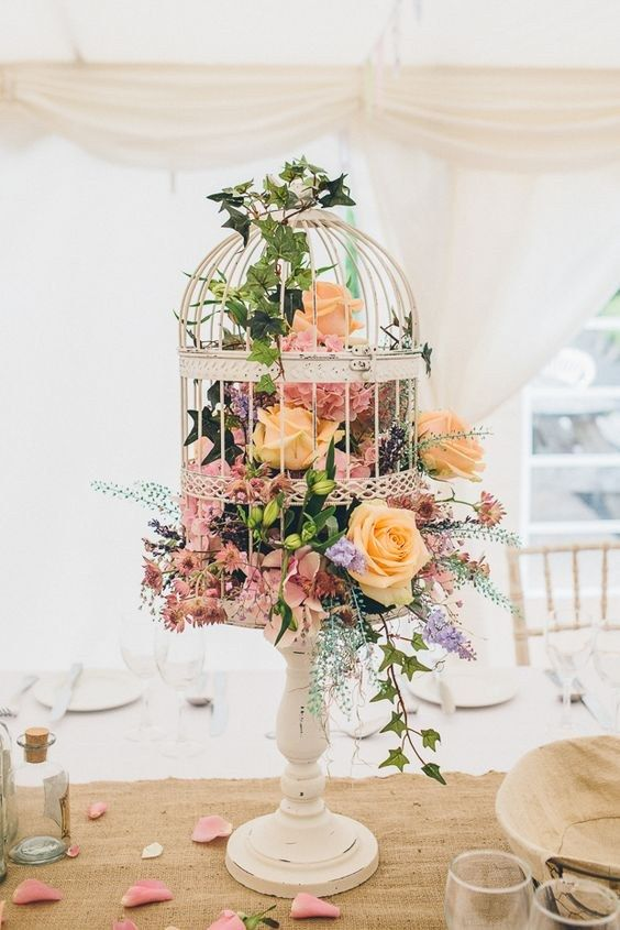a birdcage on a wooden stand filled with lush florals in yellow, pink and lilac