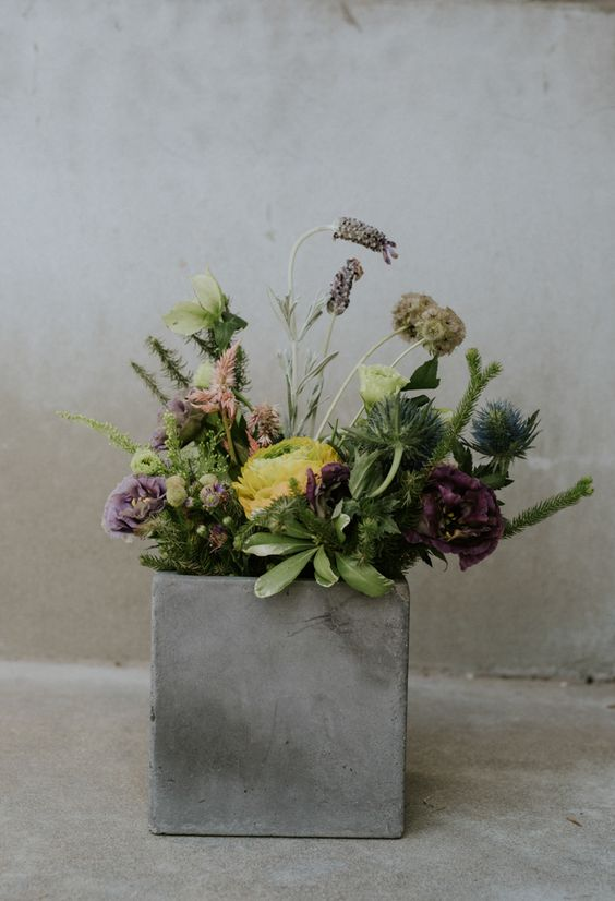 a concrete box with greenery and blooms for a modern wedding centerpiece
