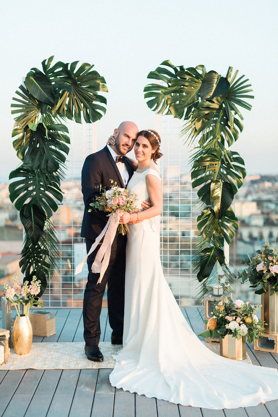 a disappearing wedding backdrop with tropical leaves looks ethereal and chic