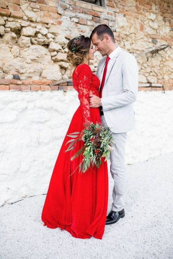 a red wedding dress with lace sleeves and bodice and a textural greenery bouquet